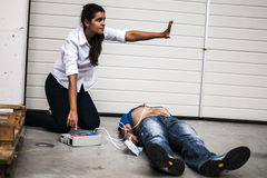 Girl assisting an unconscious man. Girl assisting an unconscious men after cardiac arrest with defibrillator Stock Images