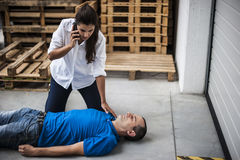 Girl assisting an unconscious man. Girl assisting an unconscious men after fatal accident with cardiopulmonary resuscitation and defibrillator Stock Photo