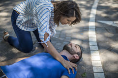 Girl assists an unconscious guy after accident. Girl helping an unconscious guy with cpr and cardiac massage Stock Image