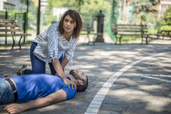 Girl assists an unconscious guy after accident. Girl helping an unconscious guy with cpr and cardiac massage Royalty Free Stock Image