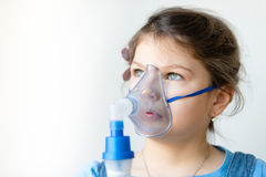 Girl with asthma inhaler. Girl with asthma problems making inhalation with mask on her face. Inhalation treatment of respiratory diseases stock photos