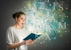 Girl with astonishment looks in the book Royalty Free Stock Photos