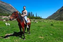 Girl astride a horse Stock Image