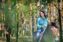 Girl astride a horse. Beautiful, young girl rides astride a horse Stock Photography