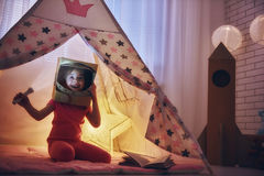 Girl in an astronaut costume. Child in an astronaut costume playing and dreaming of becoming a spacemen. Happy kid plays in tent. Funny lovely girl having fun in Royalty Free Stock Photography