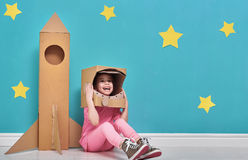 Girl in an astronaut costume. Child girl in an astronaut costume with toy rocket playing and dreaming of becoming a spacemen. Portrait of funny kid on a stock images