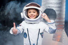 Girl in astronaut costume. Cute little girl in astronaut costume showing thumb up and smiling at camera royalty free stock image