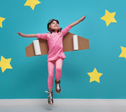 Girl in an astronaut costume. Little child girl in an astronaut costume is playing and dreaming of becoming a spaceman. Portrait of funny kid on a background of Stock Photos
