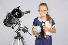 Girl astronomer is a telescope with a globe and books in the hands Stock Photos