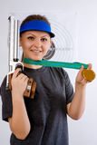 Girl athlete. On bullet shooting keeps in hand gun and medal Royalty Free Stock Photo