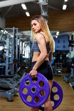 Girl athlete with a barbell in the hands of the gym.  Royalty Free Stock Photo