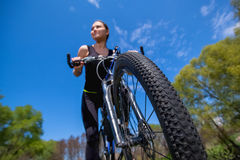 Girl athlete in black tracksuit rides a bike in the morning in the park. Stock Photos