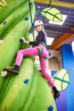 Girl athlete climbing on artifical green tree Stock Photo