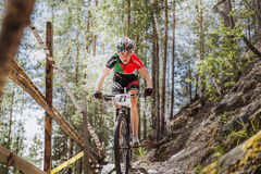 Girl athlete cyclist rides down mountain a wooden bridge Royalty Free Stock Photography