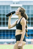 Girl athlete drinking water Stock Images