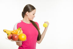 Girl athlete dumbbell raises his hand and other holding a fruit Stock Image