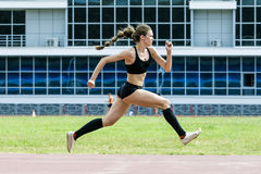 Girl athlete execution of triple jump. Girl athlete jumping triple jump in summer stadium. beautiful and young woman athlete royalty free stock image