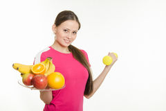 Girl athlete holding a plate of fruit and dumbbell Stock Photos