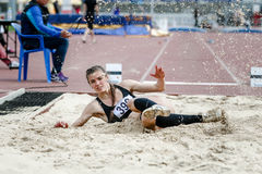 Girl athlete long jump. Beautiful young woman athlete at competitions long jump. splashes of white sand upon landing. successful attempt Stock Photo