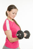 Girl athlete is looking at dumbbell in hand Stock Image