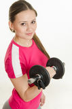 Girl athlete looking up holding a dumbbell in her hand Stock Images
