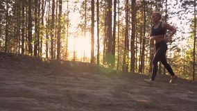 Girl athlete on a morning run. A muscular girl runs uphill at sunrise in the rays of the sun. slow motion