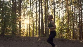 Girl athlete on a morning run. A muscular girl runs uphill at sunrise in the rays of the sun. Young girl on run training in forest. Athlete in sportswear on stock footage