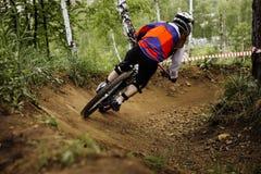 Girl athlete mountain biker down from mountain Royalty Free Stock Photo