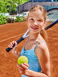 Girl athlete  with racket and ball on  tennis. Teenager girl athlete with racket and ball on  brown tennis court Royalty Free Stock Photos