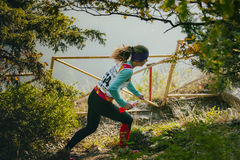 Girl athlete running through forest, in her hands a bottle of water isotonic Stock Photography