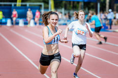 The girl athlete runs 400 m at competitions Stock Photos