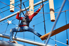 Girl athlete runs an obstacle course in climbing amusement park Royalty Free Stock Image