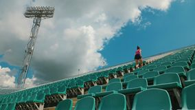 Young girl running upstairs at a stadium. Girl athlete runs the stairs in the stadium. Training before the competition. Slow motion shot stock footage