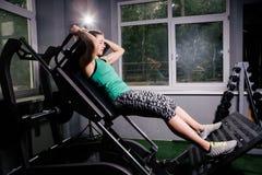 Girl athlete on the simulator doing leg exercises royalty free stock images