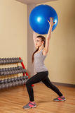 Girl athlete squats with fitball. Royalty Free Stock Photo