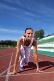 Girl athlete at the stadium is preparing to start on summer day stock photo