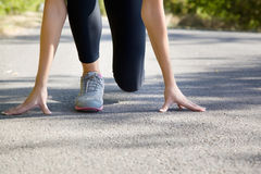 Girl athlete at the start. Close-up of girl's legs on start before jogging Royalty Free Stock Photography