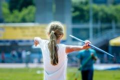 Girl athlete throwing javelin. Rear view of girl athlete in sportswear throwing javelin Royalty Free Stock Photos