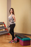 Girl athlete trains biceps with dumbbells. Stock Photos