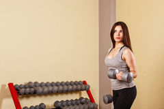Girl athlete trains biceps with dumbbells. Stock Images