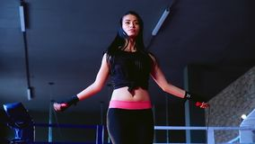 Slow motion, close-up charming cute slim brunette woman athlete jumps on rope training in gym for boxing. Slow motion, low-angle shot close-up charming cute slim stock footage