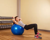 Girl athlete trains at a press fitball. Stock Photos