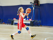 Girl athlete in uniform playing basketball Stock Image
