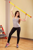 Girl athlete warming up with fitbar. Stock Photos