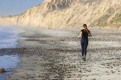 Girl in Athletic Clothing Jogging on Torrey Pines State Beach San Diego California stock images