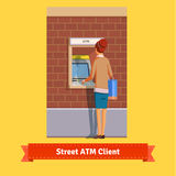 Girl at ATM machine doing deposit or withdrawal Royalty Free Stock Photos