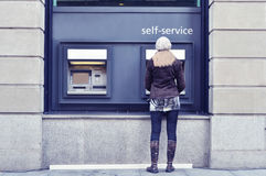 Girl at ATM. Girl on the street at ATM Royalty Free Stock Image