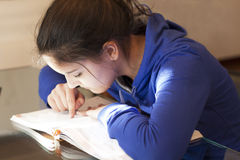 Girl attentively studying a textbook Royalty Free Stock Photos