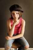 Girl with attitude. Beautiful young female child wearing a newsboy cap and ripped jeans Stock Photos