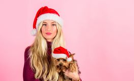 Girl attractive blonde hold dog pet pink background. Woman with puppy wear santa hat. Celebrate christmas with pets. Reasons to love christmas with pets. Ways royalty free stock photo